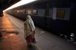 Early morning sun shines along the platform as a woman walks along the train carriage.